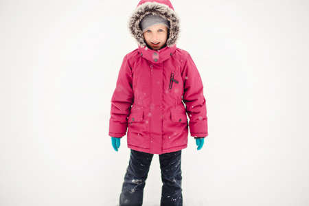 Portrait of cute funny Caucasian smiling girl child in warm clothes red pink jacket playing with snow during cold winter snowy day and looking at camera. Kids outdoor seasonal activity. Stok Fotoğraf