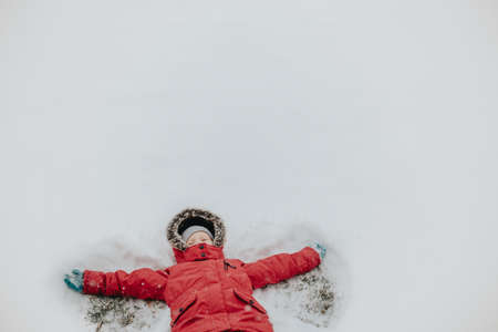 Cute adorable funny girl child in warm clothes red pink jacket making snow angel lying on ground during cold winter snowy day. Kids outdoor seasonal activity. View from top above.