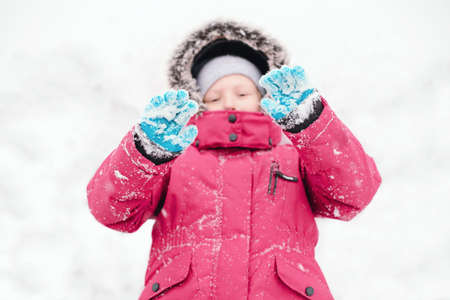 Cute adorable funny Caucasian girl child in warm clothes red pink jacket playing with snow lying on ground during cold winter snowy day.