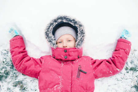 Cute adorable funny Caucasian girl child in warm clothes pink jacket making snow angel lying on ground during cold winter snowy day. Kids outdoor seasonal activity. View from top above.