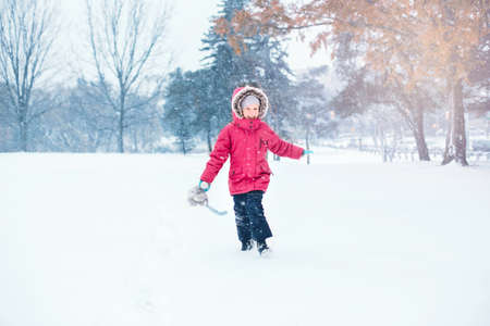 Cute adorable funny Caucasian smiling laughing girl child in warm clothes red pink jacket running in snow and having fun during cold winter snowy day. Kids outdoor seasonal activity.