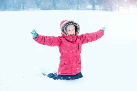 Cute adorable funny Caucasian smiling laughing girl child in warm clothes red pink jacket playing with snow having fun during cold winter snowy day at snowfall. Kids outdoor seasonal activity.