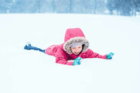 Cute funny Caucasian smiling excited girl child in warm clothes pink jacket playing with snow lying on ground during cold winter snowy day at snowfall. Kids outdoor seasonal activity.