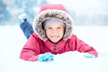Portrait of cute Caucasian smiling excited girl child in pink jacket playing with snow lying on ground during cold winter snowy day at snowfall. Kids outdoor seasonal activity. Funny face. Stok Fotoğraf