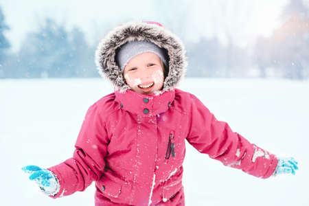 Portrait of cute Caucasian smiling laughing excited girl child in pink jacket playing with snow during cold winter snowy day at snowfall. Kids outdoor seasonal activity. Funny face.