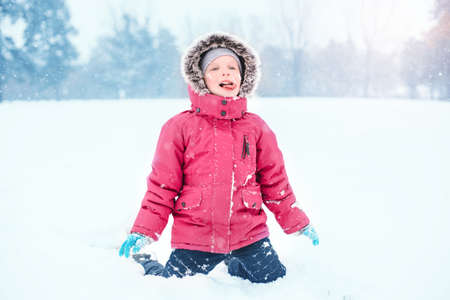 Cute adorable funny Caucasian excited girl child eating licking snow during cold winter snowy day. Kids outdoor seasonal activity. Happy candid authentic childhood lifestyle.