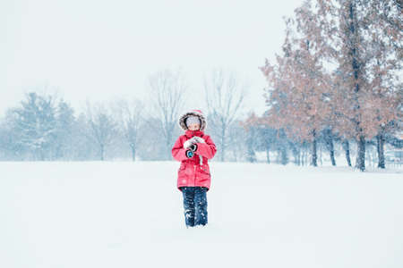 Cute adorable sad unhappy abandoned Caucasian frozen girl child with toy standing alone in park during cold winter snowy day snowfall under falling snow. Kids outdoor seasonal activity.