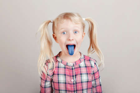 Funny blonde Caucasian girl making faces in front of camera. Child showing blue tongue on light background. Kid expressing emotions. April fool's day concept. Toned with classic blue 2020 color. Banco de Imagens