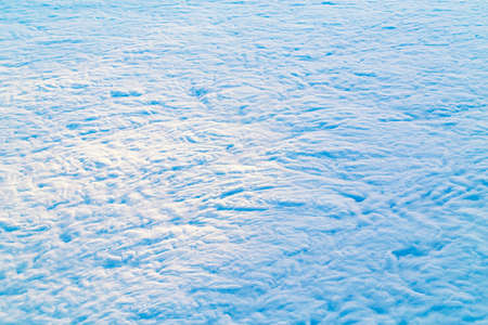 Light baby blue aquamarine sky with white blue white clouds. Serene calm idyllic view of sun light coming from large big cumulus clouds. Aerial view from above.