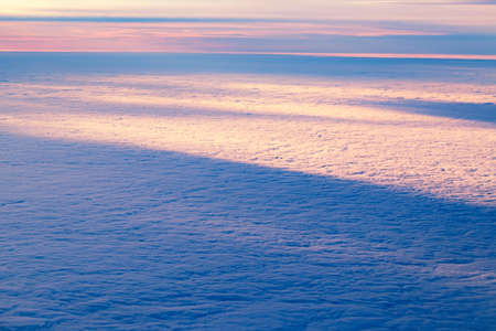 Aerial view from airplane of bright colorful pink red yellow orange sun beams in clouds on light blue sky at sunset sunrise. Evening or morning time nature. Natural eco background with copyspace.
