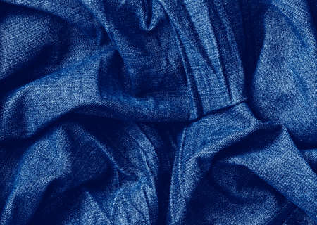 Closeup classic blue macro texture of blue jeans material fabric or clothing. Toned trendy 2020 year color background with wrinkles and folds. Dark blue monochrome backdrop wallpaper.