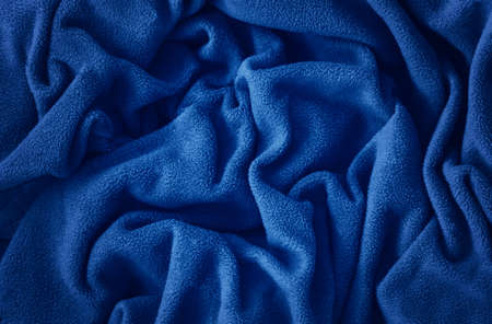 Closeup classic blue macro texture of blue fleece material fabric or clothing. Toned trendy 2020 year color background with wrinkles and folds. Dark blue monochrome backdrop wallpaper.