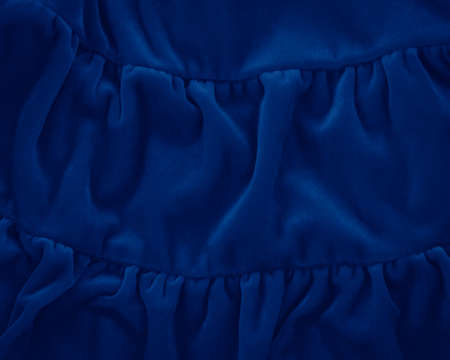 Closeup classic blue macro texture of blue velvet material fabric or clothing. Toned trendy 2020 year color background with wrinkles and folds. Dark blue monochrome backdrop wallpaper.