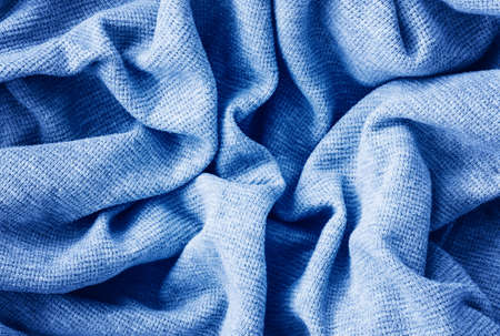 Closeup classic blue texture of knitted cotton waffle jersey material fabric or clothing. Toned trendy 2020 year color background with wrinkles and folds. Dark blue monochrome backdrop.