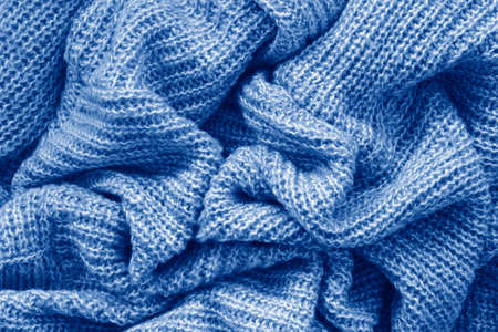 Closeup classic blue texture of knitted wool material fabric or clothing. Toned trendy 2020 year color background with wrinkles and folds. Dark blue monochrome backdrop wallpaper. Reklamní fotografie