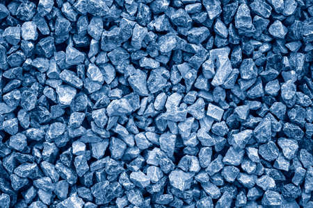 Closeup of small little broken crushed stones rocks lying on ground. Natural environmental eco background texture. Garden rubble macadam. Toned with classic blue 2020 color.
