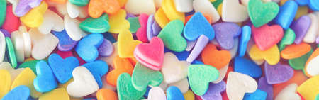 Heap of colorful candies confetti of  heart shape. Valentine Day holiday concept. Toned with retro vintage filters. Web banner header for website. Pink small lonely heart among many others.