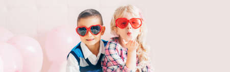 Valentine day holiday celebration. Web header banner for website. Two happy Caucasian cute funny children wearing heart shape sunglasses. Boy and girl hugging. Love, friendship and fun.