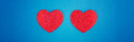 Happy Valentine Day. Beautiful card wallpaper with two red hearts in centre on blue background. Concept of love  February holiday.  Web banner header for website.