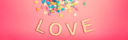 Happy Valentine Day. Beautiful card with colorful hearts candies on pink background. February holiday. Wooden words letters saying love. Web banner header for website. Reklamní fotografie
