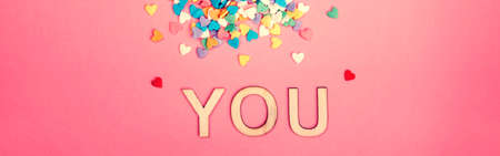 Happy Valentine Day. Beautiful card with colorful hearts candies on pink background. Concept of love. February holiday. Wooden word letters saying you.  Web banner header for website.