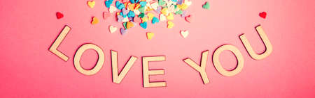 Happy Valentine Day. Beautiful card with colorful hearts candies on pink background. February holiday. Wooden words letters saying love you. Web banner header for website.