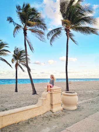 Little blonde Caucasian girl sitting relaxing dreaming on empty ocean beach in Florida. Child among tall palm trees on summer sunny day at sunset. Travel vacation kids holiday concept. Standard-Bild - 139697066