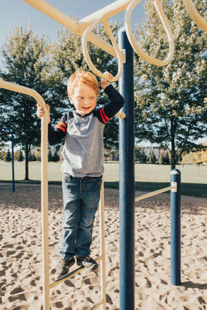 Young red-haired Caucasian boy hanging on monkey bars in park on playground. Summer outdoor activity for kids. Active preschool child doing exercises sport. Healthy happy childhood. Standard-Bild - 139682841