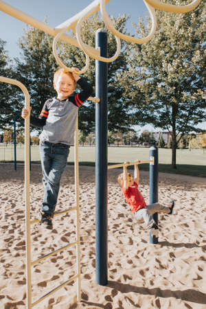 Young Caucasian boys friends hanging on monkey bars and pull-up bars in park on playground. Summer outdoor activity for kids. Active children doing exercises sport. Healthy happy childhood. Standard-Bild - 139682828
