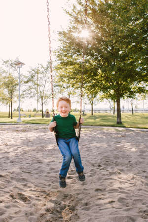 Happy smiling little preschool boy swinging on swing-set playground outside on summer day. Happy childhood lifestyle concept. Seasonal outdoor activity for kid. Standard-Bild - 139682734