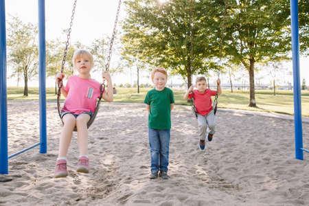 Happy smiling little preschool girl and boys friends swinging on swings at playground outside on summer day. Happy childhood lifestyle concept. Seasonal outdoor activity for kids. Standard-Bild - 139682707