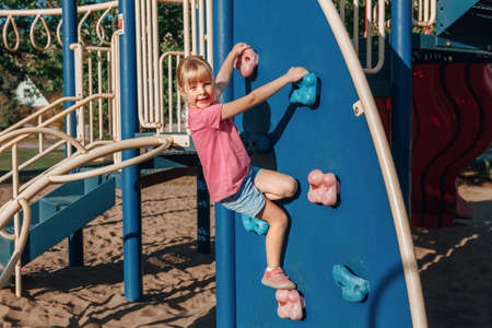 Happy smiling little preschool girl climbing rock wall at playground outside on summer day. Happy childhood lifestyle concept. Seasonal outdoor activity for kids. Standard-Bild - 139682785