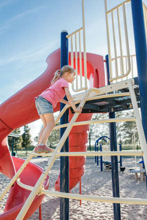 Active happy brave Caucasian girl child climbing staircase climber on playground schoolyard outdoor on summer sunny day. Seasonal kids activity outside. Authentic childhood lifestyle concept. Standard-Bild - 139682712