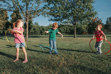 Cute smiling Caucasian preschool girl boys friends playing with hoola hoop in park outside. Kids sport activity. Lifestyle happy childhood. Summer seasonal outdoor game fun for kids children. Standard-Bild - 139697228