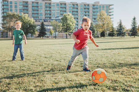 Little preschool boys friends playing soccer football on playground grass field outside. Happy authentic candid childhood lifestyle. Seasonal summer outdoor activity with ball for kids.