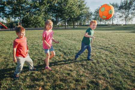 Preschool Caucasian girl and boys friends playing soccer football on playground grass field outside. Happy authentic candid childhood lifestyle. Seasonal summer outdoor activity with ball for kids. Standard-Bild - 139682792