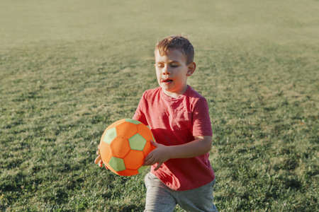 Little preschool Caucasian boy playing soccer football on playground outside. Kid carrying holding ball. Happy authentic candid childhood lifestyle. Seasonal summer outdoor activity for children. Standard-Bild - 139682726