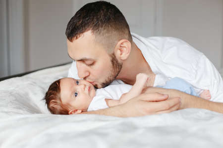 Happy Caucasian father holding newborn baby. Male bearded man parent hugging kissing child daughter son. Authentic lifestyle candid moment. Proud young dad. Family fathers day. Standard-Bild - 139682755