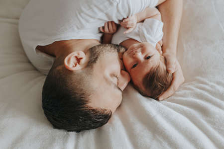 Happy Caucasian father lying on bed with newborn baby. Man parent hugging kissing child daughter son. Authentic lifestyle candid moment. Proud young dad. Family fathers day. View from top above. Standard-Bild - 139697230