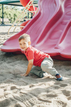 Active happy funny smiling Caucasian boy child sliding on playground schoolyard outdoor on summer sunny day. Kid having fun. Seasonal kids activity outside. Authentic childhood lifestyle concept. Standard-Bild - 139682811