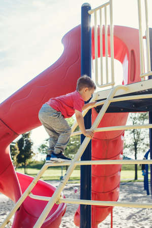 Active happy brave Caucasian boy child climbing staircase climber on playground schoolyard outdoor on summer sunny day. Seasonal kids activity outside. Authentic childhood lifestyle concept.