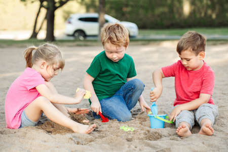 Three Caucasian children sitting in sandbox playing with beach toys. Little girl and boys friends having fun together on playground. Summer outdoor activity for kids. Leisure time lifestyle childhood. Stock Photo