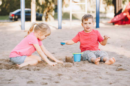 Two Caucasian children sitting in sandbox playing with beach toys. Little girl and boy friends having fun together on playground. Summer outdoor activity for kids. Leisure time lifestyle childhood.