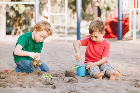 Two Caucasian children sitting in sandbox playing with beach toys. Little boys friends having fun together on playground. Summer outdoor activity for kids. Leisure time lifestyle childhood.