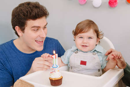 Smiling Caucasian father with baby boy celebrating his first birthday at home. Proud parent dad together with child kid toddler. Cupcake food with one lit candle. Happy birthday lifestyle concept. Standard-Bild - 141483079