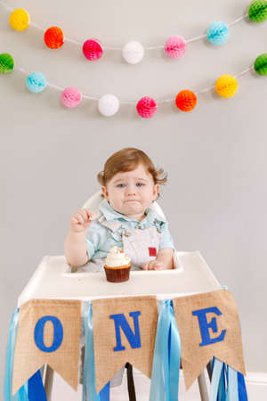 Cute adorable sad upset Caucasian baby boy celebrating his first birthday at home. Pensive child kid toddler sitting in high chair table eating tasty cupcake dessert. Happy birthday lifestyle concept. Standard-Bild - 141482775