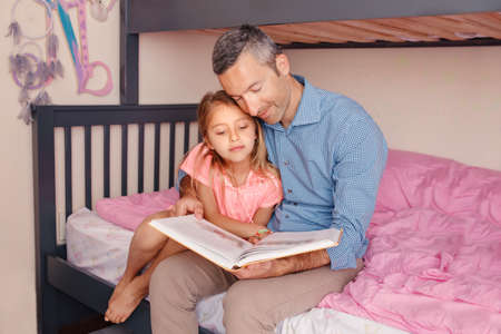 Dad reading book to pre-teen daughter girl. Happy family of two sitting on bed in bedroom. Smiling father and child at home spending time together. Education and authentic lifestyle childhood. Standard-Bild - 141483027
