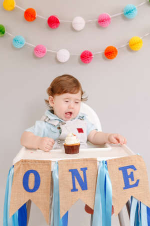 Cute adorable sad upset Caucasian baby boy celebrating his first birthday at home. Pensive child kid toddler sitting in high chair table eating tasty cupcake dessert. Happy birthday lifestyle concept. Standard-Bild - 141482992