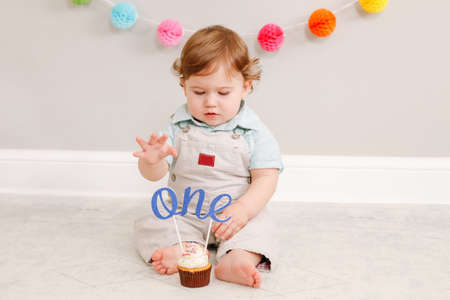 Happy cute Caucasian baby boy celebrating his first birthday at home. Child kid toddler sitting on floor in room. Tasty cupcake dessert with cake topper word one. Happy birthday concept. Standard-Bild - 141482734