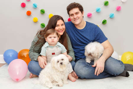 Caucasian family with baby boy celebrating his first birthday at home. Proud parents mother and father dad together with child kid toddler and dogs pets. Happy birthday lifestyle concept. Standard-Bild - 141482853